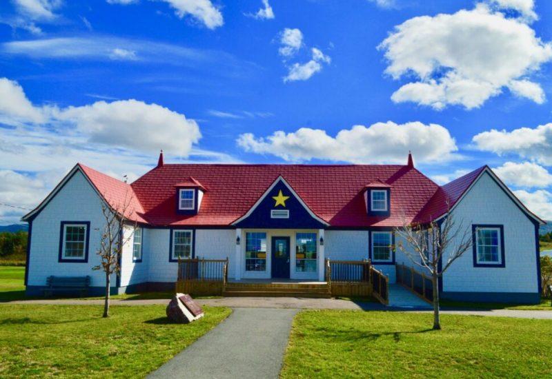 Édifice aux couleurs blanc et bleu avec toit rouge par une journée ensoleillée.