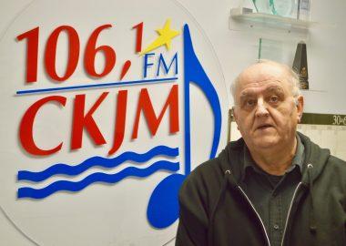 Un homme assez âgé en avant du logo de Radio CKJM