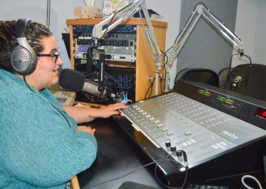 Dame avec chandail bleu et des écouteurs parlant dans un micro en avant d'une console de radio.