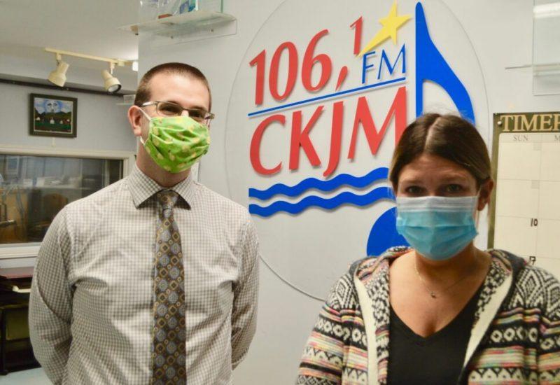 Homme avec chemise et cravate brune portant un masque vert et femme avec chandail multicolore en avant du logo de Radio CKJM.