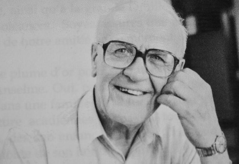 Homme âgé avec lunettes et chemise blanche souriant à la caméra.