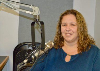Dame aux cheveux longs avec chandail bleu en avant d,un micro dans un studio de radio.