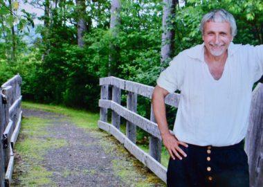 Homme interprète dans un costume d'époque à côté d'un pont en pleine campagne.