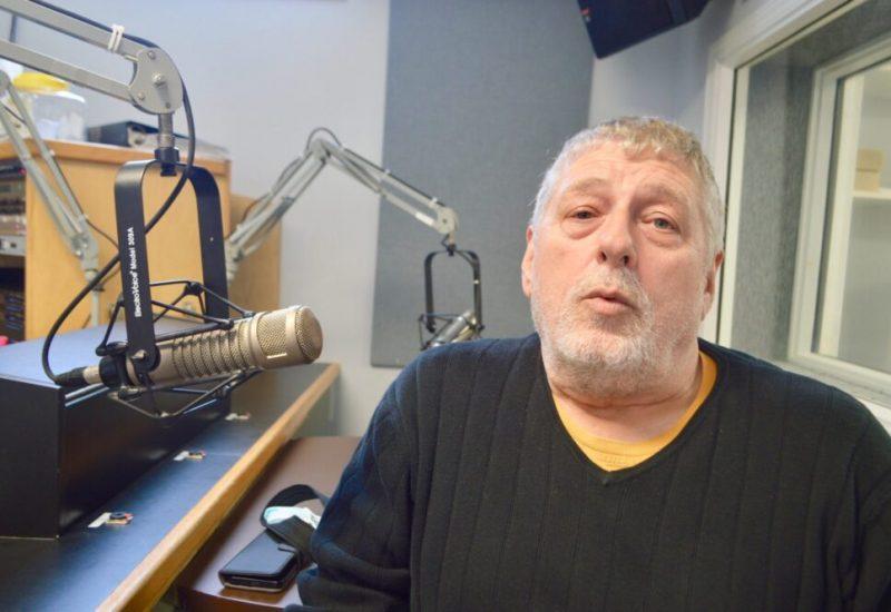 Homme avec chandail noir assis à côté d,un micro dans un studio de radio.