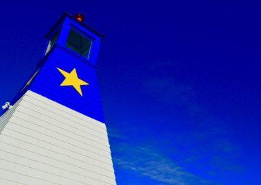 Phare avec étoile jaune contre un ciel bleu.