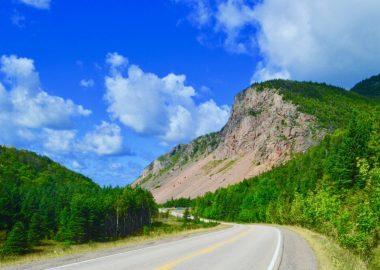 La route principale avec une grande falaise en arrière plan lors d'une journée ensoleillée dans la campagne.