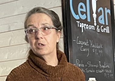 Mayor Darlene Norman speaks at an event in front of a chalkboard sign for the Cellar Tap Room and Grill.