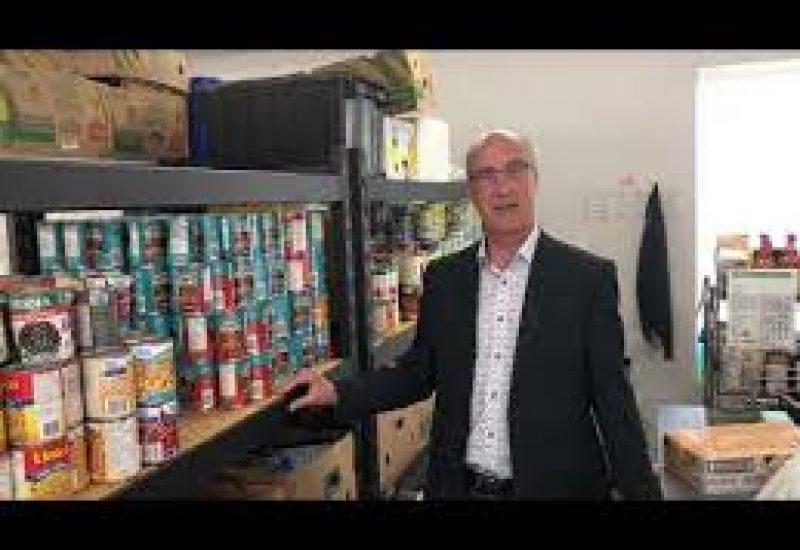 Dave Murray pictured in the Abbotsford Food Bank near some shelves of canned goods.