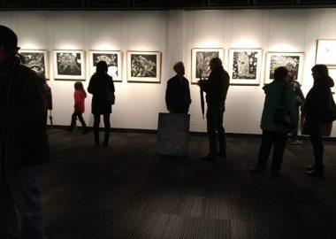 Plusieurs personnes assistent à une exposition. Six oeuvres sont exposées sur un mur blanc