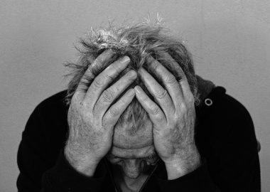 Un photo en noir et blanc d'une personne qui se tient la tête entre les mains.