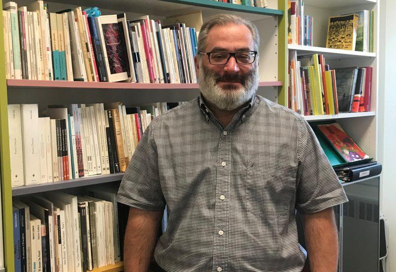 Denis Duval devant une bibliothèque remplie de livres