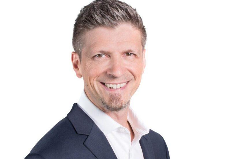 Denis Girard est photographié sur un fond blanc. Il est habillé d'une chemise blanche et d'un veston noir.