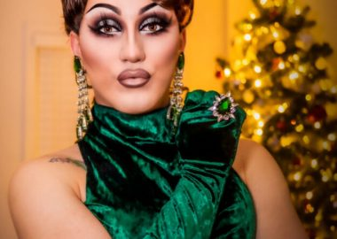 Ottawa drag queen, Devona Coe, in a green dress and green gloves.