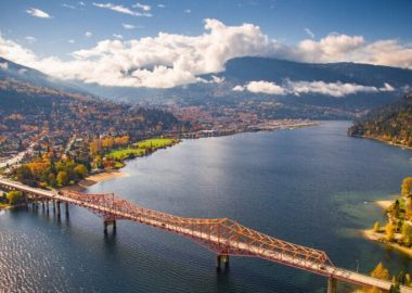 An aerial shot of Nelson BC on a sunny, summer day with Kootenay Lake and the Orange Bridge featured.