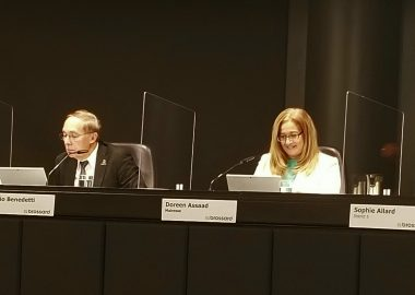 Le conseiller de Brossard Claudio Benedetti et la mairesse Doreen Assaad sont assis côte à côte à la table du conseil municipal. Monsieur Benedetti est vêtu d'un complet noir, d'une chemise blanche et d'une cravate rouge. Madame Assaad a un chandail turquoise et un veston blanc.