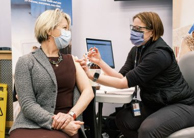 A woman wearing black gives a vaccine shot to Dr. Bonnie Henry in her arm in a medical clinic