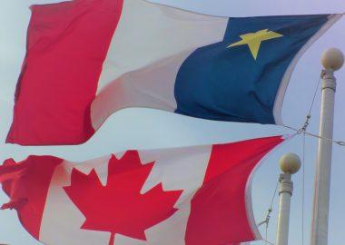Les drapeaux acadien et canadien flottant au vent