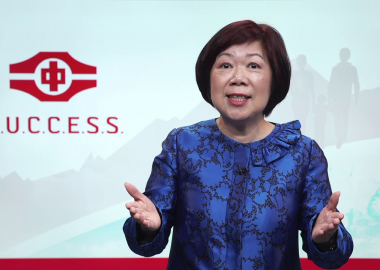 Queenie Choo stands in front of a SUCCESS green, grey and red backdrop