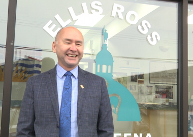 Skeena MLA Ellis Ross stands in front of the window to his public office in Kitimat village