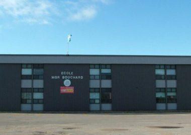 École primaire Mgr Bouchard, bâtisse grise foncée dans un stationnement vide avec un ciel bleu dégagé en arrière plan.