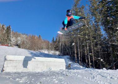 Une jeune fille faisant un grab en snowboard. Paysage d'hiver