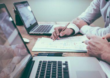 Deux personnes discutant d'un planimprimée sur une feuille posée entre deux ordinateurs