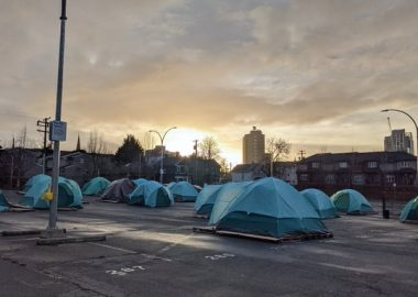Numerous blue tents are seen in downtown Victoria at sundown