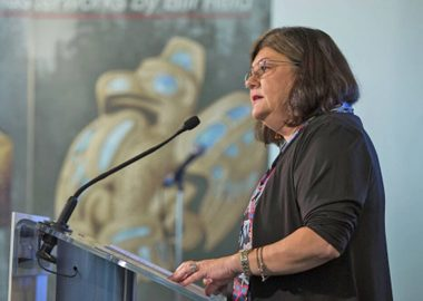 Dr. Shannon MacDonald stands at a metal podium with a microphone at a press conference.