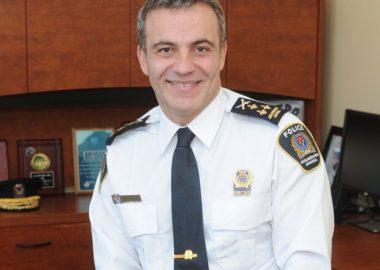 Fady Dagher, un homme, pose dans son bureau. Il porte une chemise blanche avec l'écusson de la police de longueuil et une cravate noir.