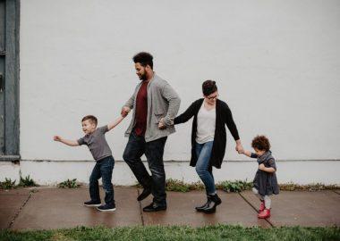 Une famille de 4 marche main dans la main sur un trottoir légèrement mouillé