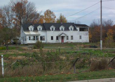 Une grande maison blanche derrière un champ