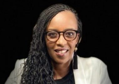 Florence Ngenzebuhoro vêtu d'un veston blanc sur fond noir