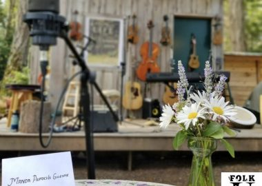 A name card and flower bouquet with microphone in the foreground, string instruments hanging on an outdoor wall in the background.