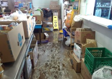 Cardboard boxes of food sit on stainless steel counters and shelves. The floor is covered in suds and water.