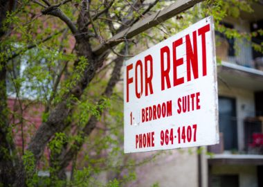 A red and white For Rent sign is seen against a tree and building background.
