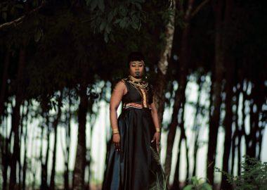 Djely Tapa portant robe noir, marron, bleu et motifs multicolores, colliers africains, maquillage de scène sur fond extérieur d'arbres