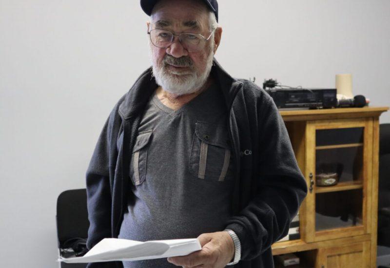 Un homme d'âge mûr portant casque, lunettes et coupe-vent tient une liasse de documents dans ses mains