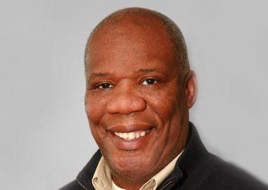 Guy-Marie Joseph souriant sur fond gris