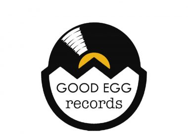 The black and white and yellow Good Egg Records Logo with half Vinyl, half Egg