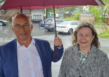 A man and a woman stand under an umbrella in the rain