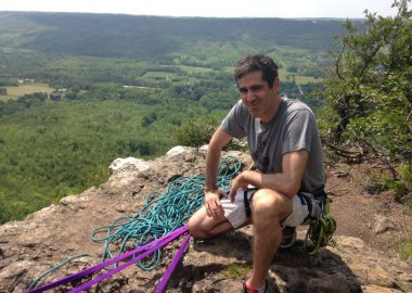 Man with climbing rope near cliffside