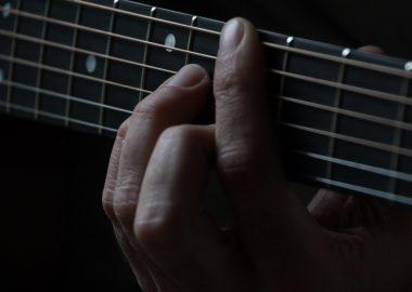 Une main pinçant les cordes d'une guitare