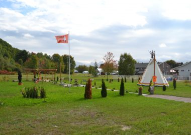 A photo of the Pontiac Native Community's healing garden in Mansfield, featuring a teepee, orange flag and plants arranged in a circle.