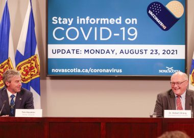 Two men sit behind a desk with Nova Scotia flags behind them