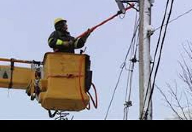 A lineman clearing snow from the power lines