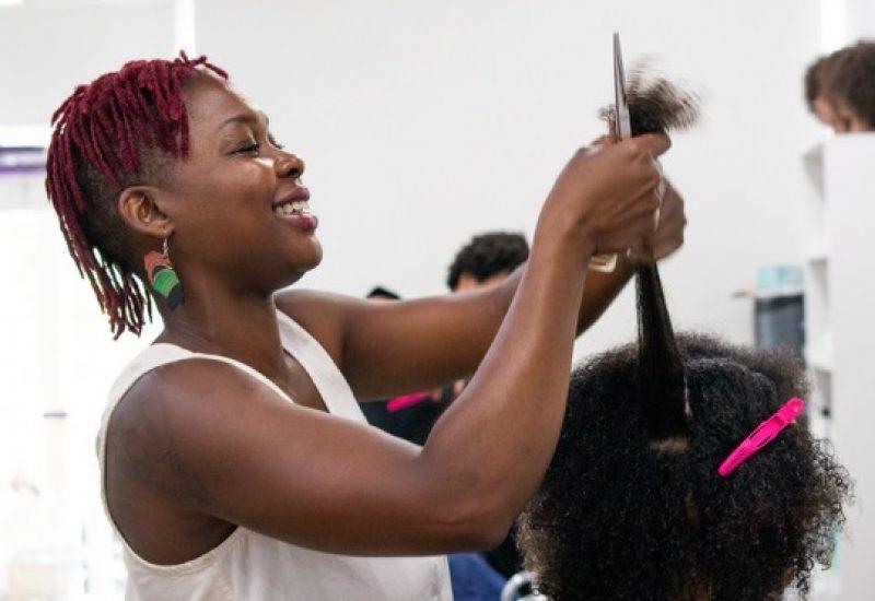 A woman styling hair inside of a salon in Ottawa