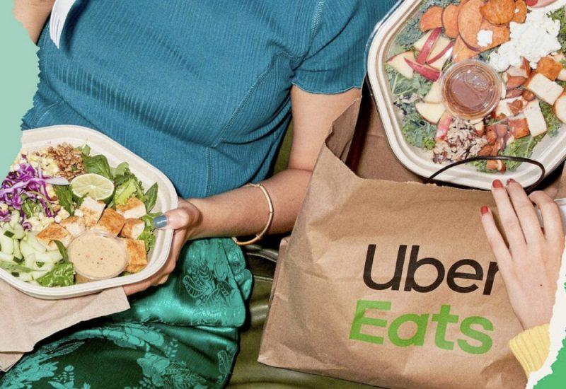 Une personne mange une salade alors qu'une deuxième sort une salade d'un sac Uber Eats.