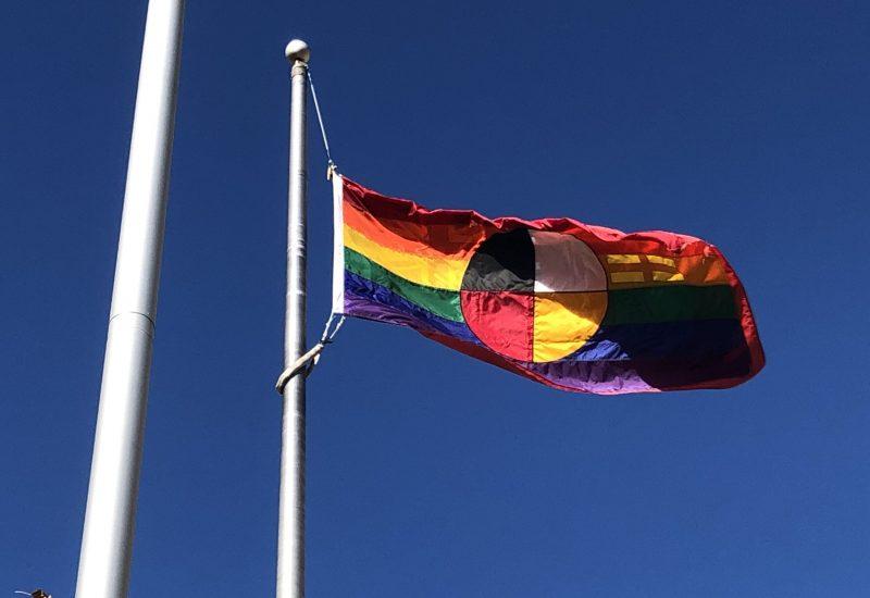 Un drapeau arc-en-ciel contient la roue médicinal autochtone au centre.