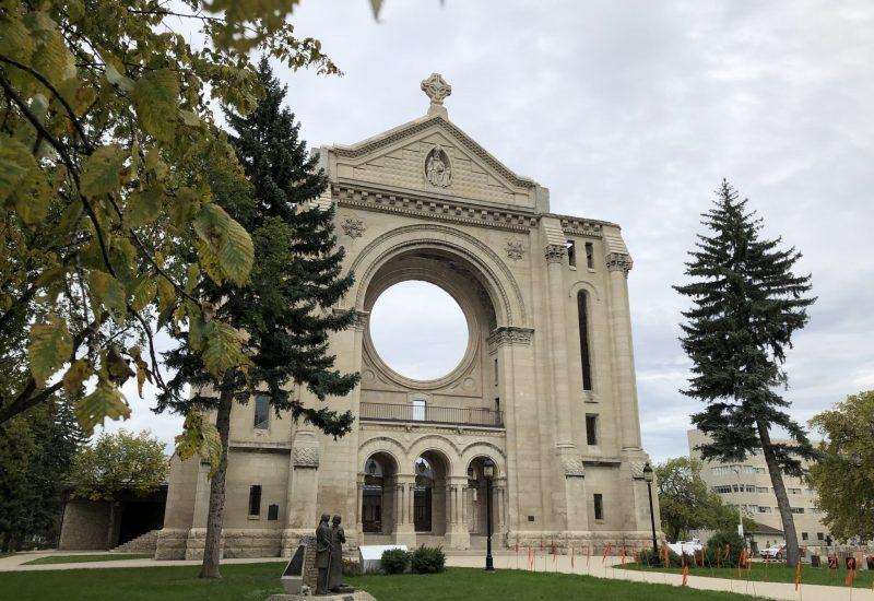 La grande facade de la cathédrale devant un ciel nuageux et des branches d'arbres en avant-plan.