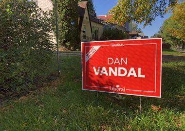 Une affiche rouge de Dan Vandal est plantée dans l'herbe devant une maison dans l'arrière plan.